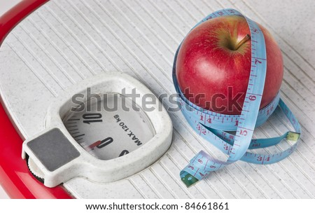apple and measuring tape on the floor scales isolated on white