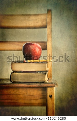 Apple and old books on school chair with vintage feel