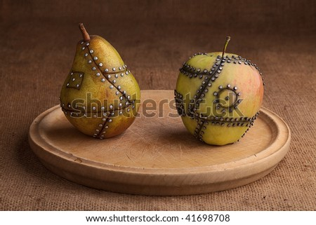 apple and pear manipulated fruit with nails holding it together genetic modification gmo concept