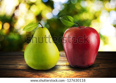 Apple and Pear on wood with summer scene background