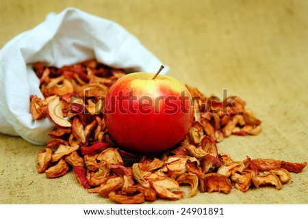 Apple and pocket of dessicated apples on the flax background