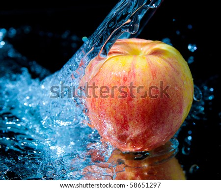 Apple and splash water over black background