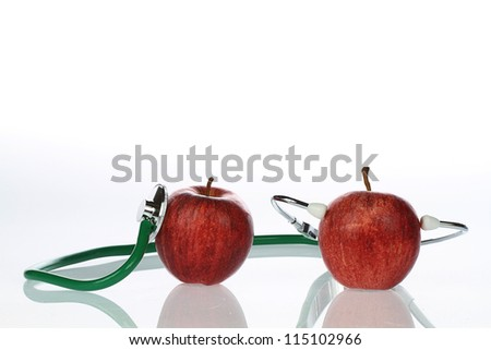 apple and stetoskop on a white background