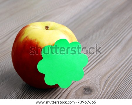 Apple and sticky note on wooden background