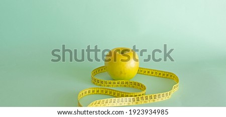 Apple and tape measure on green color background.Healthy lifestyle and weight loss concept Stok fotoğraf ©
