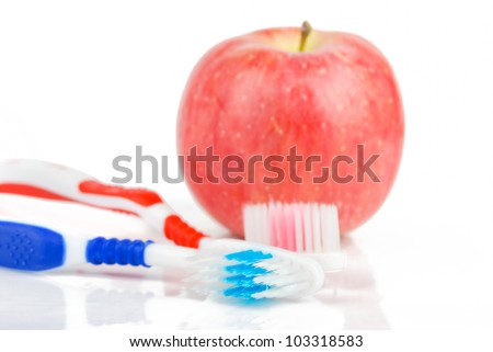 Apple and toothbrush on white background