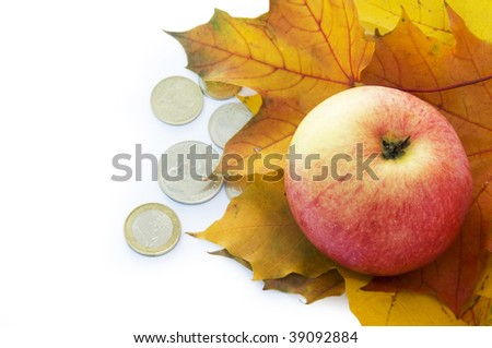 Apple, autumn leaves and coins. - stock photo