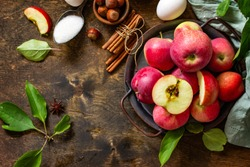 Apple baking seasonal concept. Ingredients for apple pie (red apple, flour, eggs, anise, sugar, hazelnut and cinnamon) on a rustic wooden table. Top view flat lay. Free space for your text.