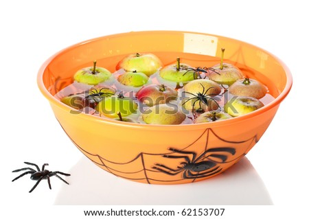 Apple bobbing at Halloween with floating apples in spider bowl on white background