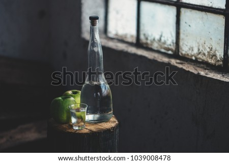 Apple brandy, rustic retro atmosphere. Bottle and single shot glass with alcohol drink and two green apple fruit.