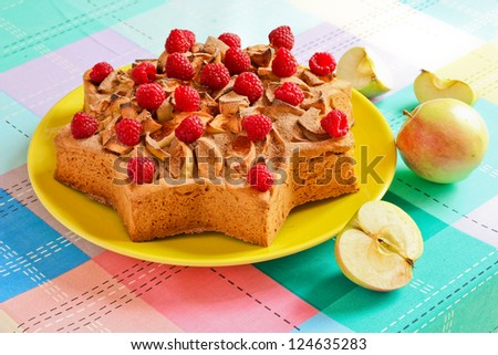 Apple cake in the shape of a star. Adorned with raspberries and apples
