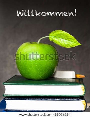 "Apple, chalk and pencil on textbooks against blackboard with text ""Welcome!"" in the German language. School concept"