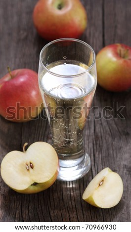 Apple cider and apples on rustic wooden table
