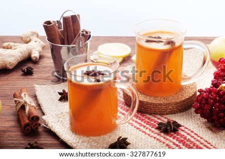 Apple cider in glass cups on a dark wooden background; cinnamon; star anise; the concept of home-made cider