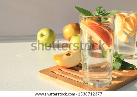 Apple cider, juice or fruit drink in a glass on a sunny table. The concept of diet and weight loss. Apples help cleanse the body and reduce weight. Healthy nutrition #1538712377