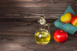 Apple cider vinegar in a glass decanter on a dark wooden table. Apples nearby.