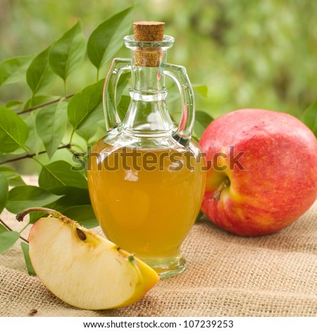 Apple cider vinegar in glass bottle, selective focus - stock photo