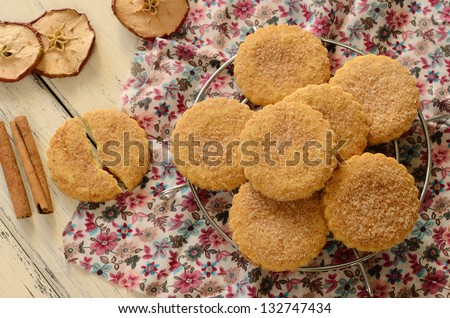 Apple cookies powdered with sugar and cinnamon on wooden table