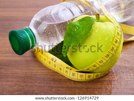 Apple core, bottled water for healthy life over a wooden background