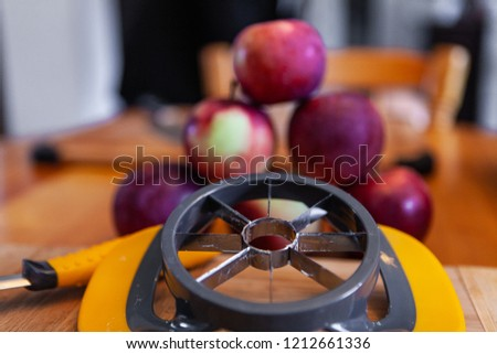 Apple corer, pyramid of apples and peeler displayed on the kitchen's table - Closeup picture taken as part of an apple cider making workshop, in an indoors family environment