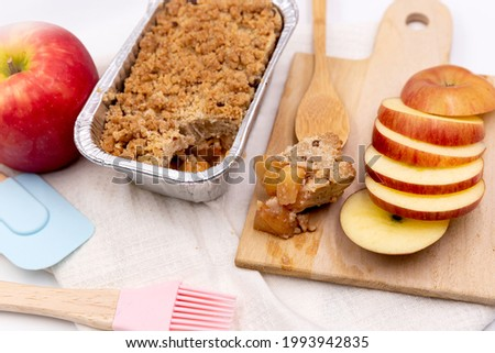 Apple crumble homemade put in foil box bowl near slice apple white cloth background. Foto stock ©