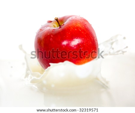 Apple falling into cream or milk and splashing