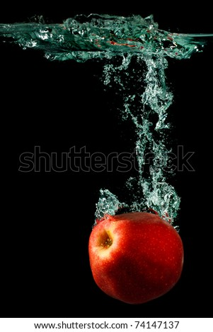 apple falling to water with splash over black background