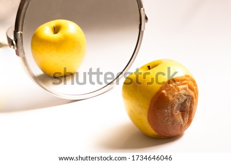 Apple in good condition looking at itself in the mirror while its back is rotten. Psychological concept, deception Сток-фото ©