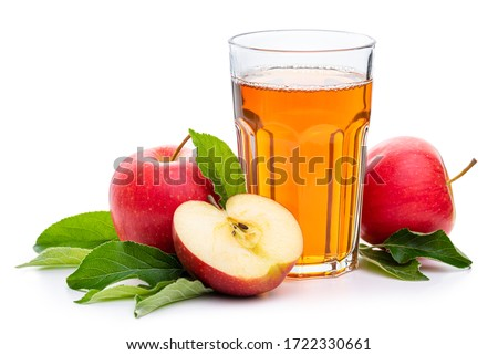 Apple juice in a glass surrounded by red apples and green leaves. Isolate on a white background.