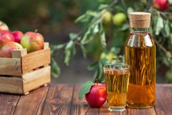 apple juice in glass and bottle with ripe fruits on wooden table outdoors. Summer refreshing drink