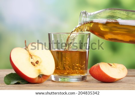 Apple juice pouring from red apples fruits in summer into a glass