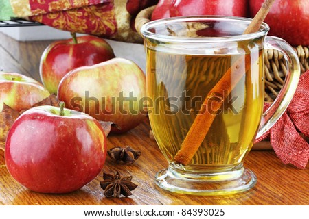 Apple Juice with cinnamon bark, anise stars and fresh apples. Shallow depth of field with selective focus on juice. Reflection can be seen in table.