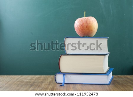 Apple on a pile of books. In the background blank chalkboard. Space for text and graphics.