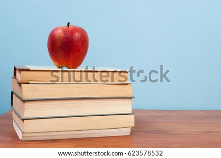 apple on a pile of books on a...