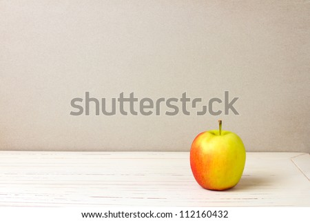 Apple on white wooden table and grey grunge background