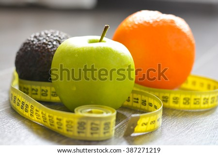Apple, orange and avocado with measuring tape suggesting diet concept #387271219