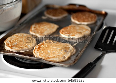 Apple pancakes cooking on the hot stove griddle.  Shallow depth of field.