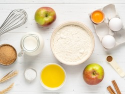 Apple pancakes or apple muffins ingredients top view. Flour, eggs in eggholder, bottle of milk, brown sugar, cinnamon powder, fresh apples, melted butter and baking powder. White wooden background.