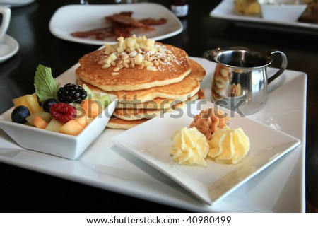 apple pancakes with maple butter and fresh fruit for breakfast