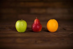 Apple, pear and orange on a wooden table