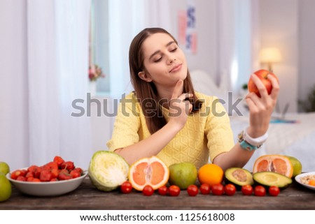 Stock Photo Apple per day. Musing teen girl admiring apple and smiling