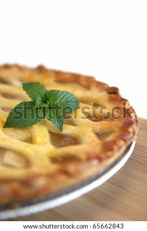 Apple pie on a counter with fresh mint on top