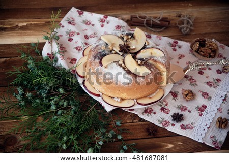 apple pie on a wooden table, decoration nuts and cinnamon, autumn harvest #481687081