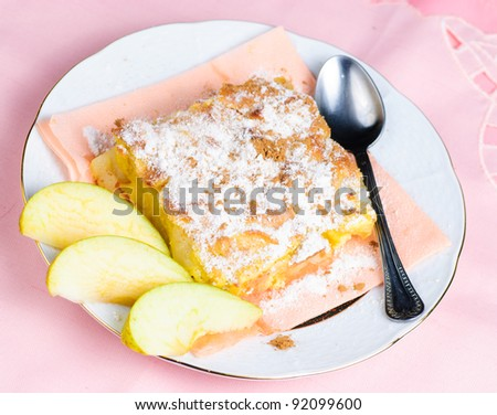 Apple pie on plate with spoon and pink placemat on background