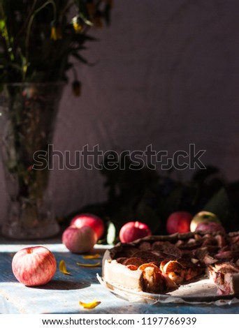 Apple pie on wooden blue rustic background. Hello autumn picture. Apples, pie, yellow flowers in a kitchen