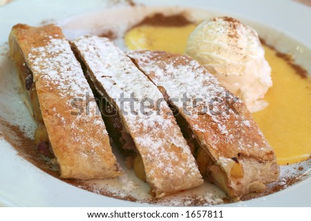 Apple pie (strudel) and vanilla ice-cream. Sugar powder, cinnamon, cacao and  citrus dressing.