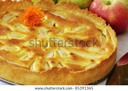 Apple pie with a marigold flower and apples in the background