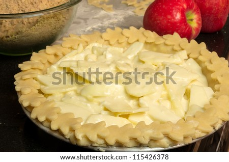 Apple pie with apples and bowl ready for the oven