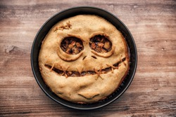 Apple pie with scary face on a wooden table