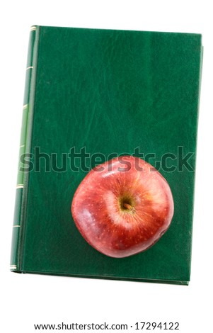 Apple red on a green book seen from above a over white background